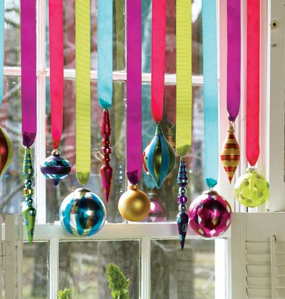hanging colorful bulbs from a curtain rod is a great way to add some cheer to your windows for all to see